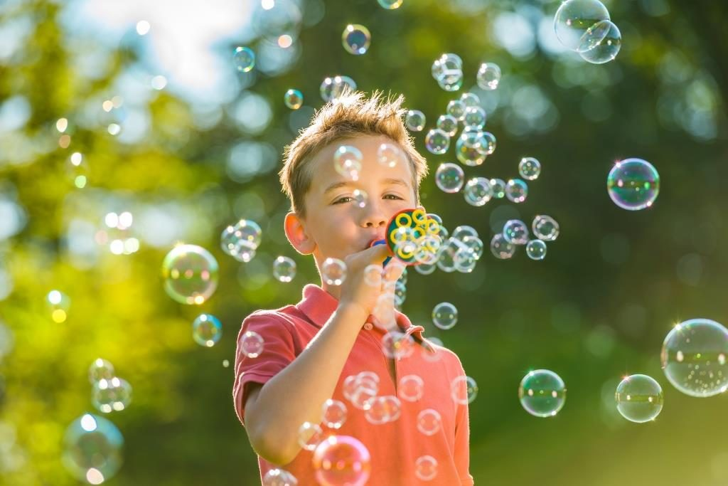 Boy blows in soap bubble trumpet by PUSTEFIX